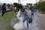 A demonstrator gets ready to throw a tear gas canister back at the police during a protest to demand the resignation of President Juan Orlando Hernandez, in Tegucigalpa, Honduras , Thursday, Oct. 24 2019. Calls for President Hernandez's resignation came after his younger brother was convicted on drug trafficking charges in New York and testimony implicated the president in his drug enterprise. (AP Photo/Elmer Martinez)