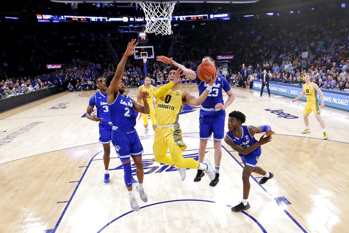 Marquette guard Markus Howard (0) goes up for a shot against Seton Hall players, from left, Romaro Gill (35), Anthony Nelson (2), Sandro Mamukelashvili (23) and Myles Cale (22) during the second half of an NCAA college basketball semifinal game in the Big East men's tournament, Friday, March 15, 2019, in New York. Seton Hall won 81-79. (AP Photo/Julio Cortez)