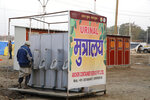 In this Monday, Jan. 14, 2019, photo, a devotee uses newly put up portable toilet at the tent city for the spiritual-cleansing Kumbh Festival in Prayagraj, India. The skies over the confluence of sacred rivers in north India where millions of Hindu priests and pilgrims have come to wash away their sins for the Kumbh Mela, or pitcher festival, that begins this week are thick with toxic dust, a sign that Indian government officials are struggling to grapple with India's worsening air pollution. (AP Photo/Rajesh Kumar Singh)