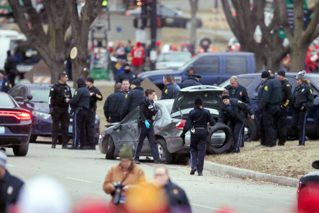 Law enforcement personnel surround a car after it was stopped as the driver approached the crowd near Union Station attending the Super Bowl parade and rally for the Kansas City Chief in Kansas City, Mo., Wednesday, Feb. 5, 2020. (AP Photo/Orlin Wagner)