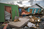 A man stands next to a destroyed house as a dog named Francoise rests on a mattress in the rubble left by Hurricane Dorian in Abaco, Bahamas, Monday, Sept. 16, 2019. Dorian hit the northern Bahamas on Sept. 1, with sustained winds of 185 mph (295 kph), unleashing flooding that reached up to 25 feet (8 meters) in some areas. (AP Photo/Ramon Espinosa)