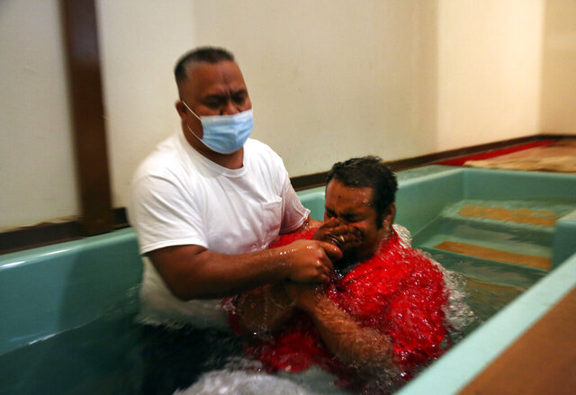 Pastor Luke Jesse of the First Marshallese Throne in Jouj church wears a mask as he baptizes Danny Baro on Sunday, Nov. 22, 2020, in Noel, Mo. After the coronavirus swept through the town of about 1,800 people, the First Marshallese Throne in Jouj and four other churches that worship at the building of the Community Baptist Church experienced a faith revival with an estimated 50 baptisms in three months. (AP Photo/Jessie Wardarski)