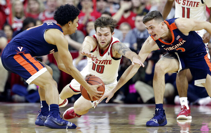 Virginia's Kihei Clark, left, and Kyle Guy reach for a loose ball with North Carolina State's Braxton Beverly (10) during the first half of an NCAA college basketball game in Raleigh, N.C., Tuesday, Jan. 29, 2019. (AP Photo/Gerry Broome)