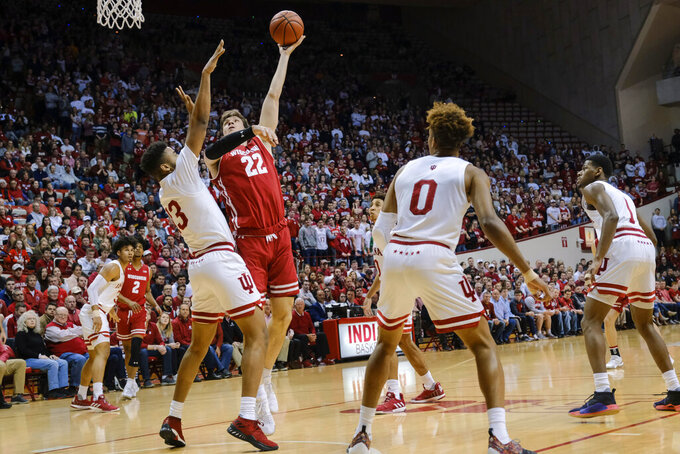 Wisconsin forward Ethan Happ (22) shoots over Indiana forward Juwan Morgan (13) during the first half of an NCAA college basketball game in Bloomington, Ind., Tuesday, Feb. 26, 2019. (AP Photo/AJ Mast)