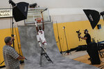 Miami Heat's Bam Adebayo stands on a ladder under a basket as he poses for a photographer during the NBA basketball team's Media Day in Miami, Monday, Sept. 27, 2021. (AP Photo/Rebecca Blackwell)