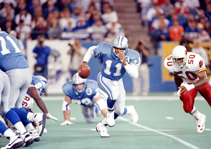 FILE - In this Sept. 26, 1993, file photo, Detroit Lions quarterback Andre Ware (11) runs from the pocket while trying to avoid the tackle of Phoenix Cardinals outside linebacker Freddie Joe Nunn (50) during the first quarter in Pontiac, Mich. The Motor City has witnessed a lot of losing seasons in the league in large part because the Lions have missed more than hit the mark with draft decisions. Taking quarterback Andre Ware seventh overall in 1990 is only one example. (AP Photo/Lennox McLendon, File)