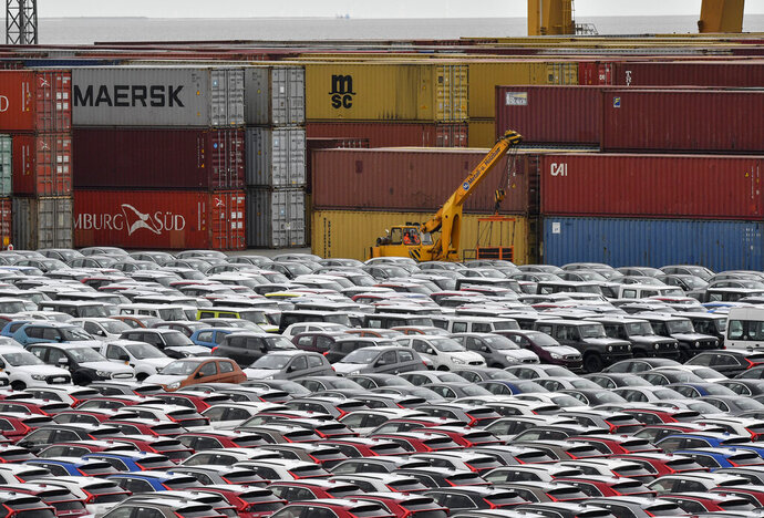 FILE - In this Thursday, May 16, 2019 photo cars for export and import are stored in front of containers at the harbor in Bremerhaven, Germany. The German economy shrank by 0.1 percent in the second quarter as global trade conflicts and troubles in the auto industry weighed on Europe's largest economy. (AP Photo/Martin Meissner, file)