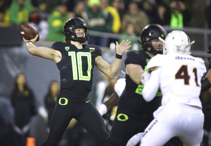 Oregon quarterback Justin Herbert, left, throws down field against Arizona State during the third quarter of an NCAA college football game Saturday, Nov. 17, 2018, in Eugene, Ore. (AP Photo/Chris Pietsch)