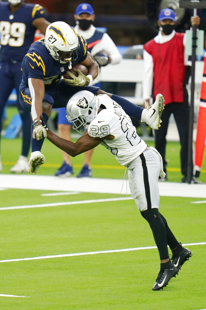 Los Angeles Chargers running back Joshua Kelley, above, tries to leap over Las Vegas Raiders free safety Lamarcus Joyner during the second half of an NFL football game Sunday, Nov. 8, 2020, in Inglewood, Calif. (AP Photo/Alex Gallardo)