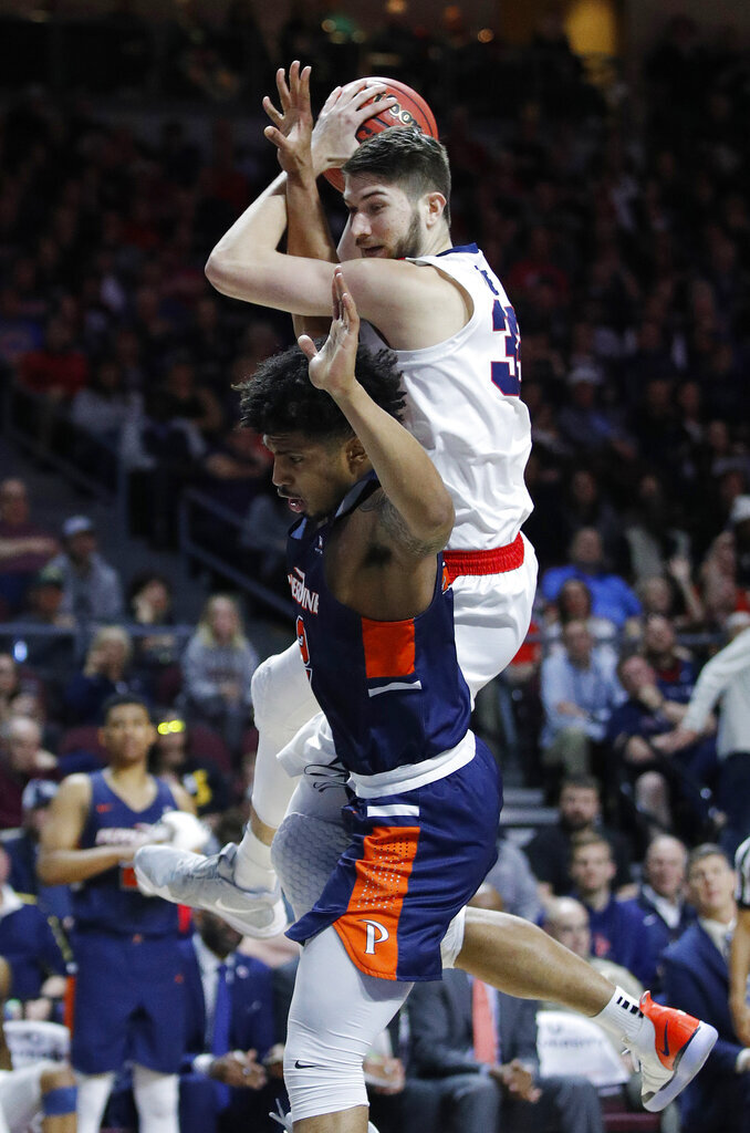 Pepperdine's Darnell Dunn, bottom, fouls Gonzaga's Killian Tillie, top, during the second half of an NCAA semifinal college basketball game at the West Coast Conference tournament, Monday, March 11, 2019, in Las Vegas. (AP Photo/John Locher)