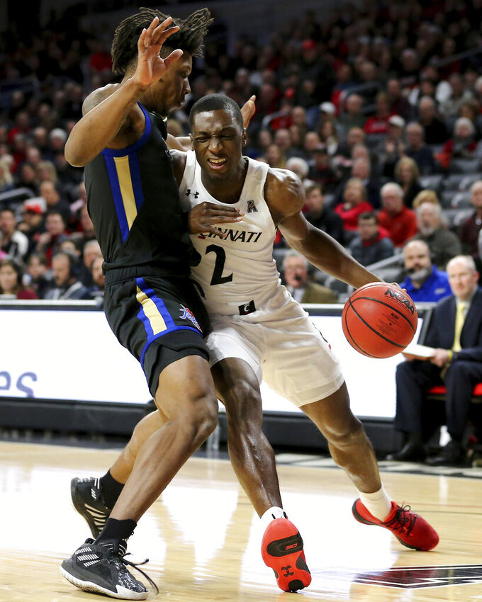 Cincinnati guard Keith Williams (2) drives to the basket as Tulsa guard Brandon Rachal (0) defends during the first half of an NCAA college basketball game Wednesday, Jan. 8, 2020, in Cincinnati. (Kareem Elagazzar/The Cincinnati Enquirer via AP)