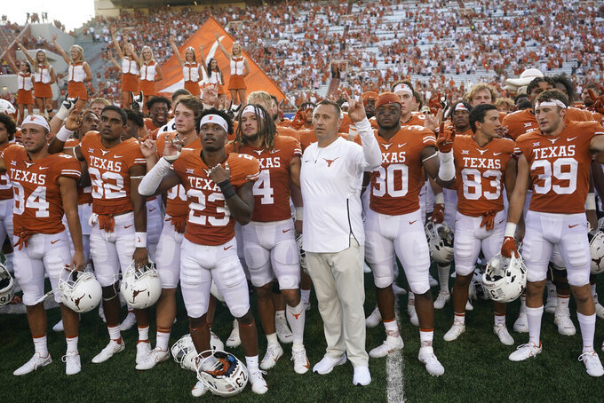 Texas coach Steve Sarkisian, center, joins players for the school song after an NCAA college football game against Louisiana-Lafayette, Saturday, Sept. 4, 2021, in Austin, Texas. (AP Photo/Eric Gay)