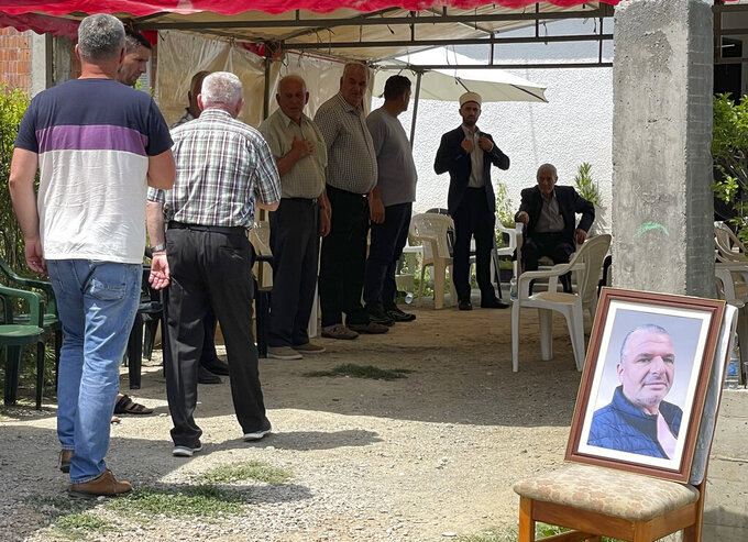 People come to the house of one of the drivers, Naser Sylmetaj (on picture, right), who also died in Sunday's road accident in Croatia, in Gjakove, 100 kilometers (60 miles) west of the capital Pristina, Monday, July 26. 2021. Kosovo is in a mourning on Monday with flags at half-staff and the parliament postponing its session due to the death of 10 Kosovars in an accident of their bus swerving while driving in Croatia.  A bus with 67 passengers, including children, and two drivers, was driving from Frankfurt, Germany to Kosovo. (AP Photo/Zenel Zhinipotoku)