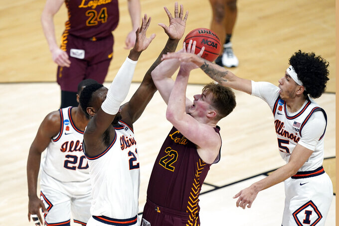 Loyola of Chicago's Jacob Hutson (22) shoots from between Illinois' Kofi Cockburn (21) and Andre Curbelo (5) during the first half of a college basketball game in the second round of the NCAA tournament at Bankers Life Fieldhouse in Indianapolis Sunday, March 21, 2021. (AP Photo/Mark Humphrey)