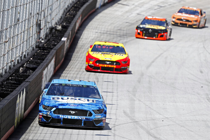 Driver Kevin Harvick (4) leads Joey Logano (22) and others down the back straight during practice for a NASCAR Cup Series auto race, Friday, Aug. 16, 2019, in Bristol, Tenn. (AP Photo/Wade Payne)