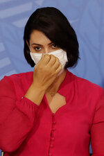 Brazil's first lady Michelle Bolsonaro adjusts her face mask during an event he attended with her husband, President Jair Bolsonaro, at the presidential palace in Brasilia, Brazil, Wednesday, July 29, 2020. According to an official statement released on Thursday, July 30, the first lady has tested positive for COVID -19. (AP Photo/Eraldo Peres)
