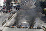 Anti-government protesters burn tires to block a main highway during ongoing protests against the government in Beirut, Lebanon, Tuesday, Jan. 14, 2020. Lebanon is facing its worst economic crisis in decades, with the local currency losing over 60% of its value to the dollar over the last weeks while sources of foreign currency have dried up. (AP Photo/Hussein Malla)