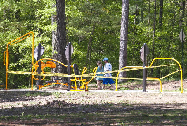 Two people walk past exercise equipment that has been taped off to keep people from using it as part of the newest measure by Mayor Harold Perrin in the effort to prevent the spread of COVID-19 on Thursday, April 9, 2020, at Craighead Forest Park in Jonesboro, Ark. (Quentin Winstine/The Jonesboro Sun via AP)
