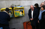 Paris mayor Anne Hidalgo, right, watches French street artist Christian Guemy, known as C215, cleaning the vandalized mailboxes with swastikas covering the face of the late Holocaust survivor and renowned French politician, Simone Veil, in Paris, Tuesday Feb.12, 2019. According to French authorities, the total of registered anti-Semitic acts rose to 541 in 2018 from 311 in 2017, a rise of 74 percent. (AP Photo/Michel Euler)