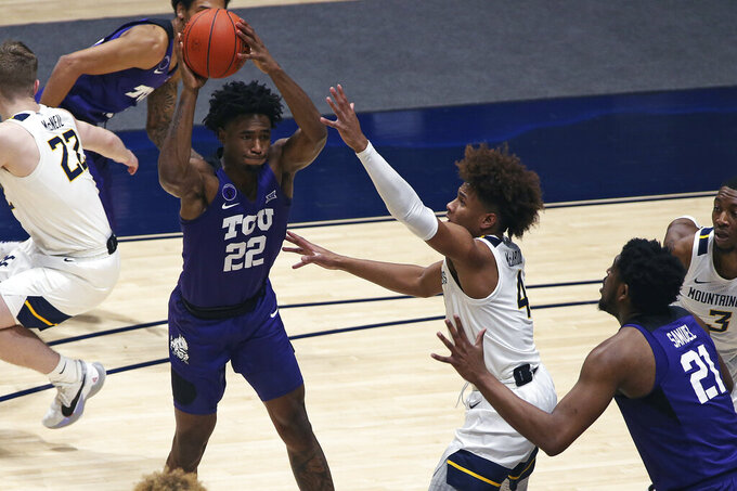 TCU guard RJ Nembhard (22) passes while defended by West Virginia guard Miles McBride (4) during the first half of an NCAA college basketball game Thursday, March 4, 2021, in Morgantown, W.Va. (AP Photo/Kathleen Batten)