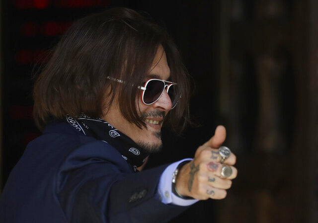 Actor Johnny Depp gestures as he arrives at the High Court in London, Friday, July 17, 2020. Depp is suing News Group Newspapers, publisher of The Sun, and the paper's executive editor, Dan Wootton, over an April 2018 article that called him a