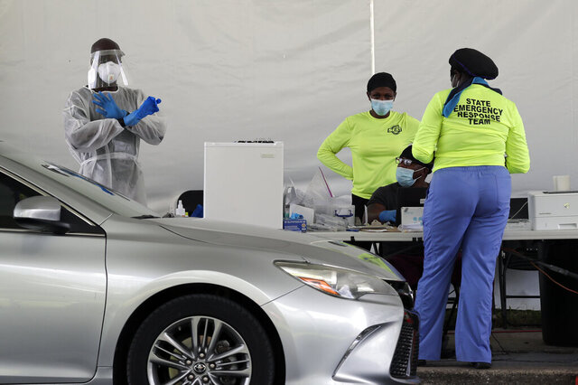 Health workers perform COVID-19 tests at the Orange County Convention Center Sunday, July 12, 2020, in Orlando, Fla. Florida on Sunday reported the largest single-day increase in positive coronavirus cases in any one state since the beginning of the pandemic. (AP Photo/John Raoux)