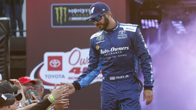 Martin Truex Jr. greets fans during driver introductions prior to the start of the NASCAR Cup series auto race at Richmond Raceway in Richmond, Va., Saturday, April 13, 2019. (AP Photo/Steve Helber)