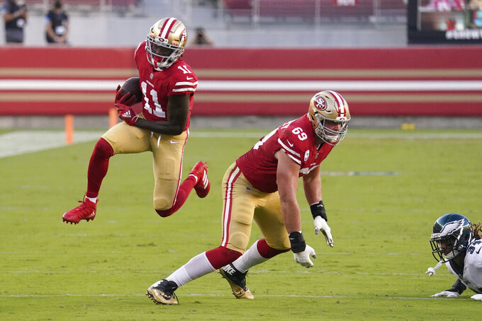 San Francisco 49ers wide receiver Brandon Aiyuk (11) runs behind offensive tackle Mike McGlinchey (69) on a touchdown run against the Philadelphia Eagles during the first half of an NFL football game in Santa Clara, Calif., Sunday, Oct. 4, 2020. (AP Photo/Tony Avelar)