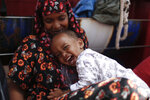 One-year-old child Mascuud, from Somalia, smiles as he hugs his mother aboard the Ocean Viking humanitarian rescue ship, in the Mediterranean Sea, Thursday, Sept. 13, 2019. Eighty-two rescued migrants remain on board the humanitarian rescue ship waiting for a European country to give them permission to disembark. (AP Photo/Renata Brito)