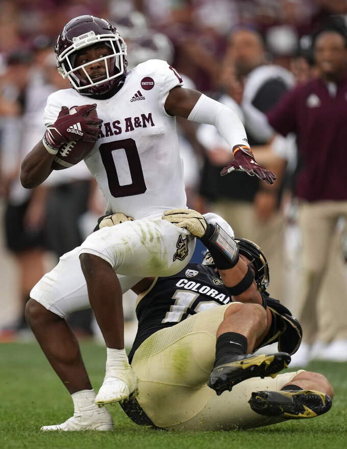 Texas A&M wide receiver Ainias Smith, left, is pulled down by Colorado linebacker Quinn Perry after catching a pass in the second half of an NCAA college football game Saturday, Sept. 11, 2021, in Denver. Texas A&M won 10-7. (AP Photo/David Zalubowski)