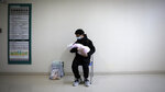 A man holds his newborn baby in hospital during the peak of the COVID-19 outbreak in Wuhan, China in a scene from the documentary
