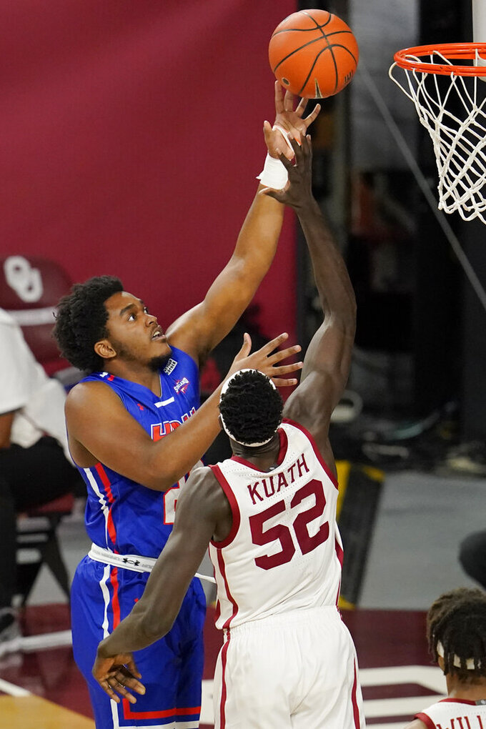 Houston Baptist guard Darius Lee, left, shoots over Oklahoma forward Kur Kuath (52) in the first half of an NCAA college basketball game Saturday, Dec. 19, 2020, in Norman, Okla. (AP Photo/Sue Ogrocki)
