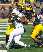 Michigan State running back Elijah Collins (24) gets tackled by Michigan defensive back Josh Metellus, top left, and linebacker Cameron McGrone (44) in the first quarter of an NCAA college football game in Ann Arbor, Mich., Saturday, Nov. 16, 2019. Michigan won 44-10. (AP Photo/Tony Ding)