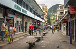 Pedestrians wear masks as they walk on a street in the capital Victoria, Mahe Island, Seychelles Thursday, Feb. 25, 2021. The president of the Indian Ocean island nation of Seychelles says he hopes enough residents will soon be vaccinated against COVID-19 to stop the spread of the virus, hoping to achieve herd immunity by mid-March by vaccinating about 70% of the population. (AP Photo/Salim Ally)