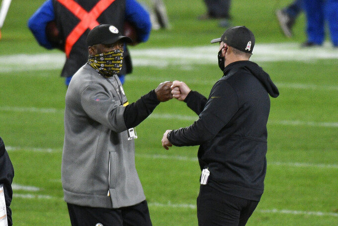 Pittsburgh Steelers head coach Mike Tomlin, left, greets Cincinnati Bengals head coach Zac Taylor on the field following an NFL football game in Pittsburgh, Sunday, Nov. 15, 2020. (AP Photo/Don Wright)