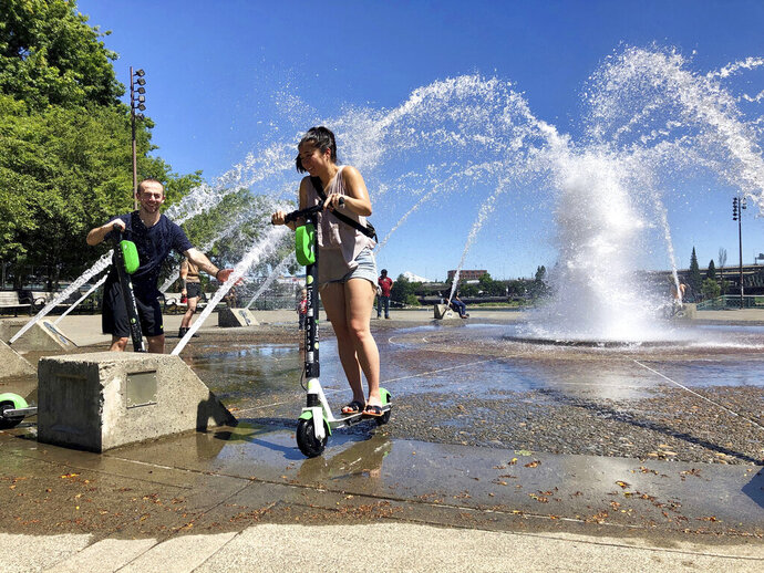 Sam Molloch, of Portland, Ore., sprays friend Alyssa Morishita, also of Portland, with water from a fountain as they both took rides under the spray on rented electric scooters to cool off in Portland on Tuesday, June 11, 2019. People in western Washington state and Oregon are wilting under warmer than normal temperatures in the 90s this week. (AP Photo/Gillian Flaccus)