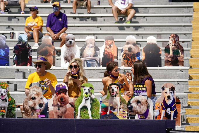 Fans sit amongst cardboard cutouts due to COVID-19 restrictions, requiring social distancing and masks, before an NCAA college football game between the LSU and the Mississippi State in Baton Rouge, La., Saturday, Sept. 26, 2020. (AP Photo/Gerald Herbert)