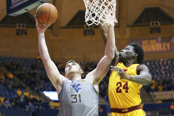 West Virginia forward Logan Routt (31) goes up for a shot as he is defended by Iowa State guard Terrence Lewis (24) during the second half of an NCAA college basketball game Wednesday, Feb. 5, 2020, in Morgantown, W.Va. (AP Photo/Kathleen Batten)