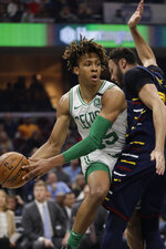 Boston Celtics' Romeo Langford, left, looks to pass against Cleveland Cavaliers' Larry Nance Jr. in the first half of an NBA basketball game, Wednesday, March 4, 2020, in Cleveland. (AP Photo/Tony Dejak)