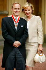 """FILE  - In this June 25, 2004 file photo, journalist Harold Evans poses for a photo with his wife Tina Brown, after he was knighted by the Prince of Wales for service to journalism. Evans, the charismatic publisher, author and muckraker, has died at 92.  His wife, fellow author-publisher Tina Brown, said he died of congestive heart failure, it was reported on Thursday, Sept. 24, 2020. He was a bold-faced name for decades, from exposing wrongdoing in 1960s London, to publishing such 1990s best-sellers as Joe Klein's """"Primary Colors.""""  (John Stillwell/PA via AP, FIle)"""