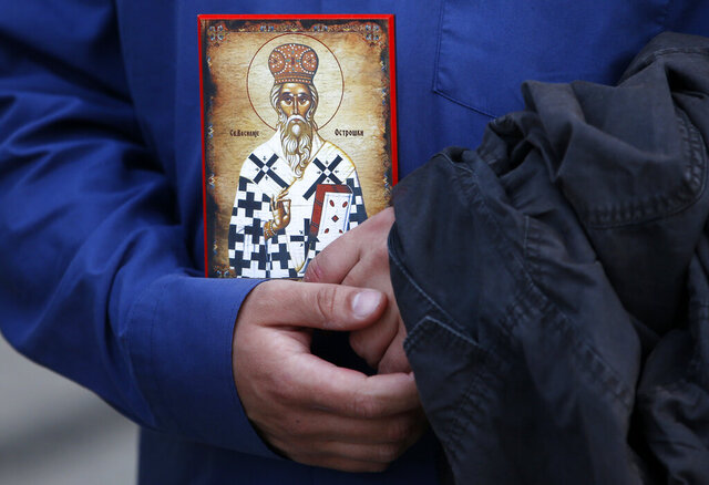A man holds an icon during a protest after arrest of Serbian Orthodox Church priests in Montenegro, in Belgrade, Serbia, Thursday, May 14, 2020. Montenegrin police said Thursday they have detained around 60 people following clashes at protests demanding the release of eight Serbian Orthodox Church priests jailed for leading a religious procession despite a ban on gatherings related to the new coronavirus outbreak. (AP Photo/Darko Vojinovic)