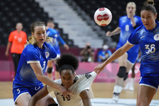 Polina Gorshkova, of the Russian Olympic Committee, left, France's Oceane Sercien Ugolin, centre, Juliia Managarova, of the Russian Olympic Committee, in action during the women's gold medal handball match between the Russian Olympic Committee and France at the 2020 Summer Olympics, Sunday, Aug. 8, 2021, in Tokyo, Japan. (AP Photo/Sergei Grits)