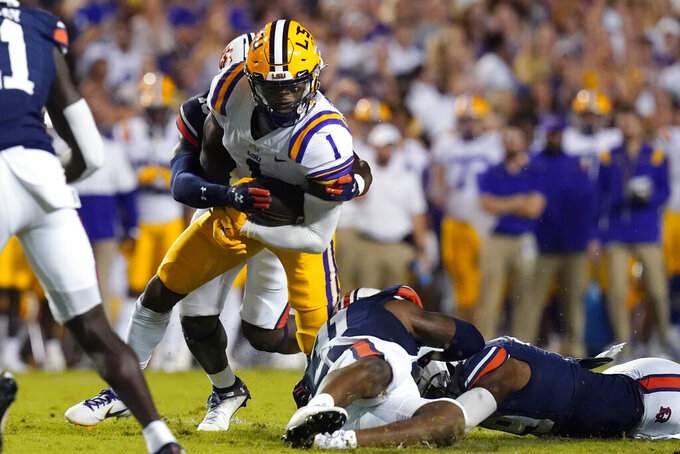LSU wide receiver Kayshon Boutte (1) carries as he is tackled by Auburn safety Zion Puckett in the first half of an NCAA college football game in Baton Rouge, La., Saturday, Oct. 2, 2021. (AP Photo/Gerald Herbert)