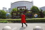 A woman walks past a decoration promoting the upcoming Road and Belt Forum outside the Chinese Foreign Ministry in Beijing on Friday, April 19, 2019. China is downplaying the political implications of its global development campaign known as the Belt and Road initiative, saying that it aims to boost multilateralism amid protectionist trends in the U.S. and elsewhere. (AP Photo/Ng Han Guan)
