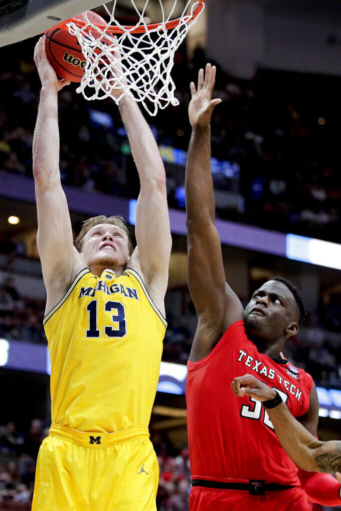 Michigan forward Ignas Brazdeikis, left, shoots over Texas Tech center Norense Odiase during the second half an NCAA men's college basketball tournament West Region semifinal Thursday, March 28, 2019, in Anaheim, Calif. (AP Photo/Jae C. Hong)