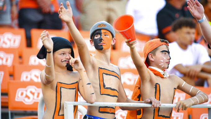 Oklahoma State fans perform the actions for the waving song at the start of an NCAA college football game against Kansas State, Saturday, Sept. 25, 2021, in Stillwater, Okla. (AP Photo/Brody Schmidt)