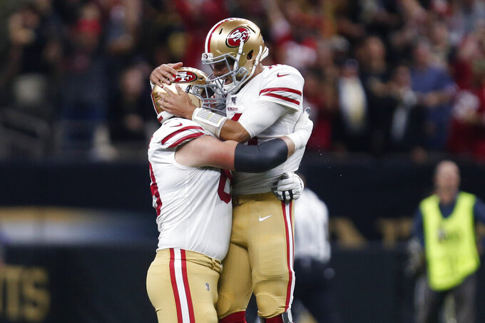 San Francisco 49ers quarterback Jimmy Garoppolo, right, celebrates his touchdown pass with offensive tackle Mike McGlinchey in the first half an NFL football game in New Orleans, Sunday, Dec. 8, 2019. (AP Photo/Butch Dill)
