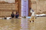 A man wades through a flooded road in the town of Shaqilab, about 15 miles (25 km) southwest of the capital, Khartoum, Sudan, Monday, Aug. 31, 2020. (AP Photo/Marwan Ali)