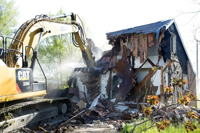 FILE - In this May 19, 2016 file photo, a demolition crew razes a dilapidated home in Detroit. Researchers at the University of Michigan say cost-savings and public safety benefits of swiftly demolishing dangerous vacant houses in Detroit could outweigh the risk of asbestos exposure to people in neighborhoods. A study of 25 emergency demolitions shows small to undetectable concentrations of asbestos. (Daniel Mears/Detroit News via AP File)
