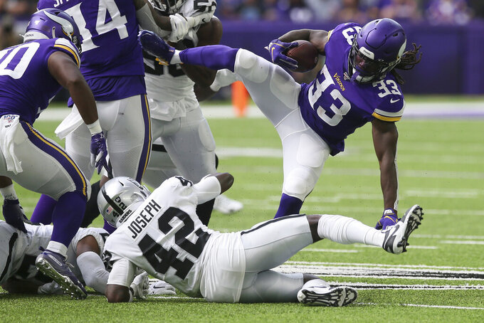 Minnesota Vikings running back Dalvin Cook (33) is upended by Oakland Raiders free safety Karl Joseph (42) during the first half of an NFL football game, Sunday, Sept. 22, 2019, in Minneapolis. (AP Photo/Jim Mone)
